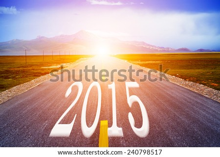 Number 2015 on road in grass field against cloudy blue sky - stock photo