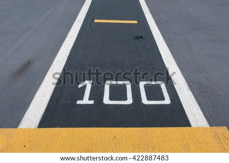 """Number """" 100 """"  on white and yellow runway. Takeoff runway and runway aircraft carrier on battleship. Public area. - stock photo"""