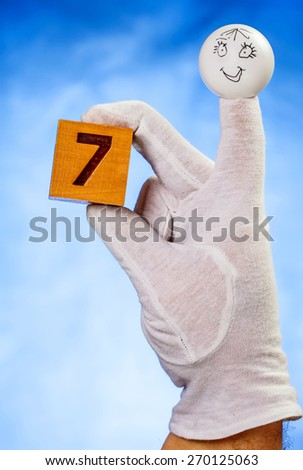 Number seven on wooden cube hold by finger puppet on blue background - stock photo
