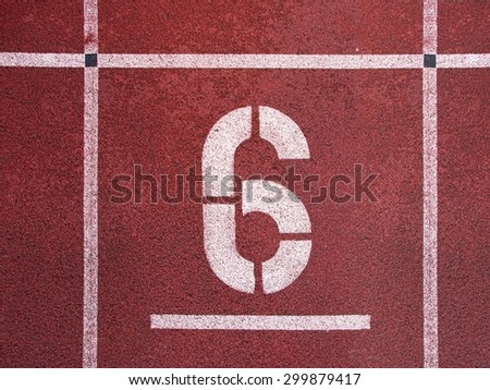 Number six. White athletic track number on red rubber racetrack, texture of running racetracks in stadium - stock photo
