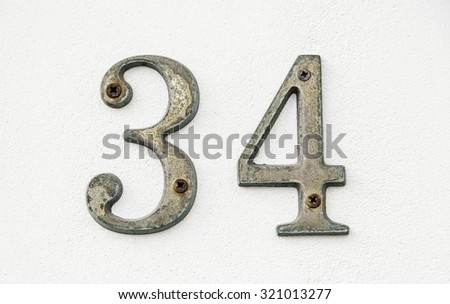 Number thirty-four on a wall, detail of an information number, even number - stock photo
