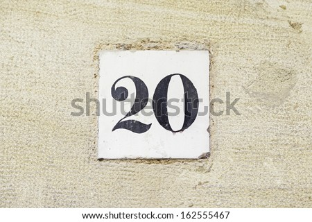 Number twenty on the wall, detail of a number of information in a house, a figure - stock photo