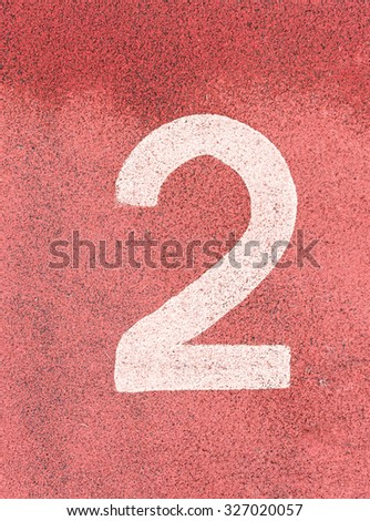 Number two,White track number on rubber racetrack, texture of running racetracks in small stadium. - stock photo