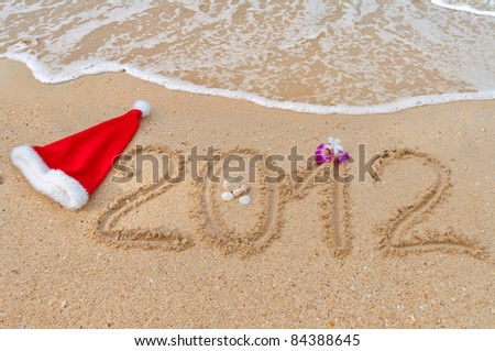 Numbers 2012 and santa hat on tropical beach sand - holiday background - stock photo