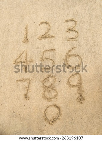 Numbers from one to ten written on a sandy beach. - stock photo
