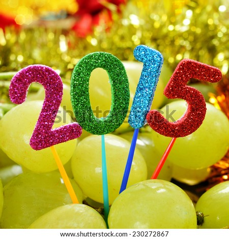 numbers of different colors forming the number 2015, as the new year, with a pile of grapes in the background - stock photo