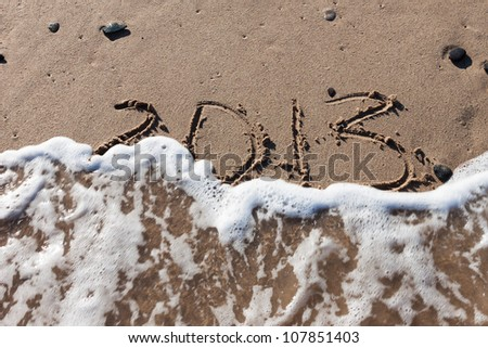 Numbers 2013 on the beach sand with wave water - stock photo