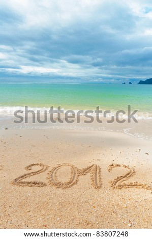 Numbers 2012 on tropical beach sand - holiday background - stock photo