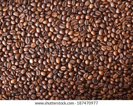 Numerous coffee beans which have been scattered all over the surface - stock photo