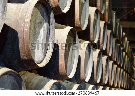 Numerous oak barrels stacked in the old cellar with aging Port wine from the vineyards Douro Valley in Portugal. Product of organic farming. - stock photo