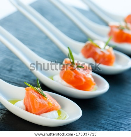 Numerous porcelain spoons with smoked salmon morsels. - stock photo