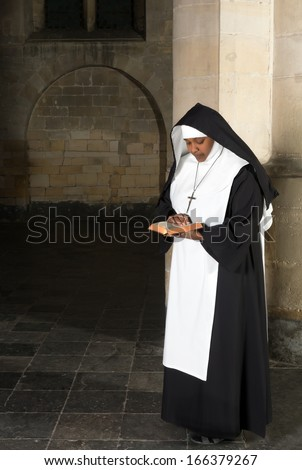Nun in habit reading the bible in a medieval church - stock photo