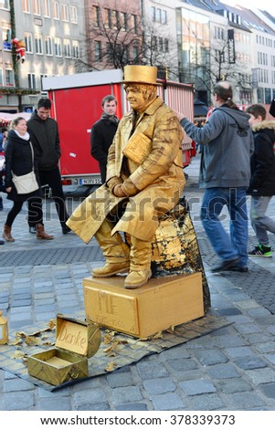 NUREMBERG - DECEMBER 6, 2015. A Street Performer imitating bronze statue in the most famous Christmas Market in Nuremberg, Germany. - stock photo