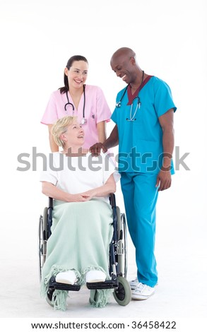 NUrse and doctor with a senior patient in a wheel chair - stock photo