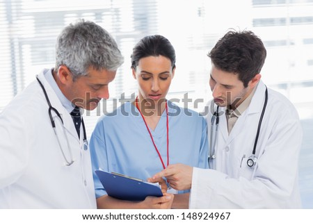 Nurse and doctors looking together a file in medical office - stock photo