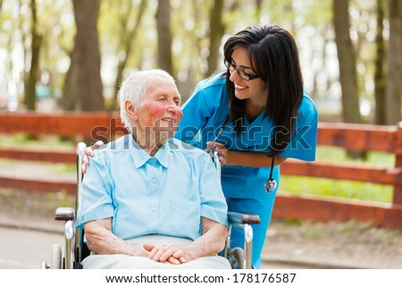 Nurse and elderly lady in wheelchair chatting outdoors. - stock photo