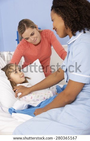 Nurse and mother at girl's bedside in hospital - stock photo