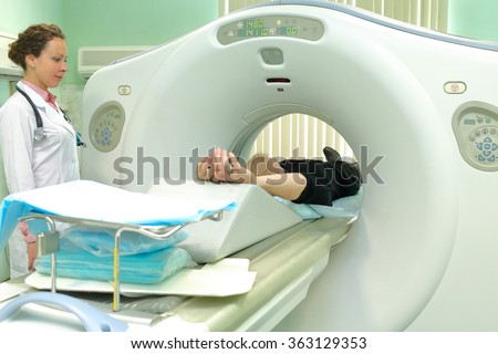 nurse and patient being scanned and diagnosed on CT (computed tomography) scanner in hospital - stock photo
