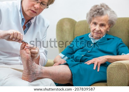 Nurse assists an elderly woman with chiropody and body care at home - stock photo