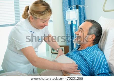 Nurse cares for a patient lying in bed in hospital - stock photo