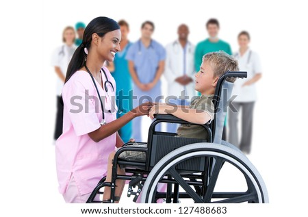 Nurse chatting with little boy in wheelchair with medical staff in background - stock photo
