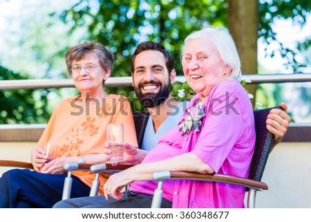 Nurse drinking coffee with seniors on terrace of retirement home - stock photo