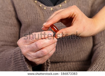 Nurse giving a pill to an  elderly wrinkled hand - stock photo