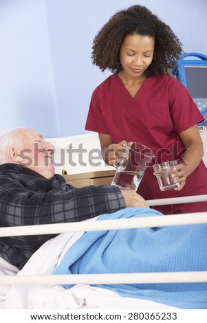 Nurse giving glass of water to senior man in hospital - stock photo