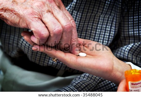 nurse giving senior man pills - stock photo