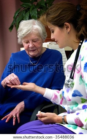 nurse giving senior woman pills - stock photo