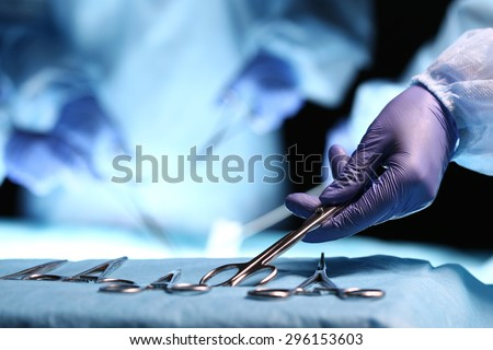 Nurse hand taking surgical instrument for group of surgeons at background operating patient in surgical theatre. Steel medical instruments ready to be used. Surgery and emergency concept - stock photo