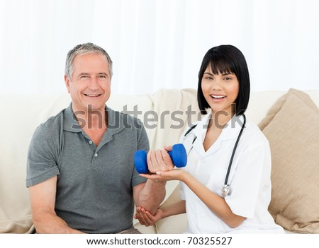 Nurse helping her patient to do exercises at home - stock photo