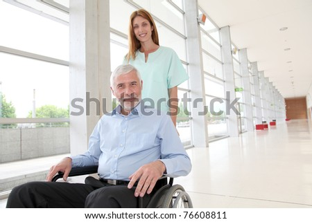Nurse helping senior man in wheelchair - stock photo