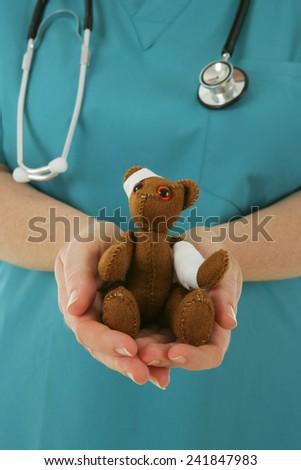 Nurse holding a bandaged teddy bear - stock photo