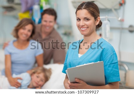 Nurse holding a clipboard next to a family in hospital ward - stock photo