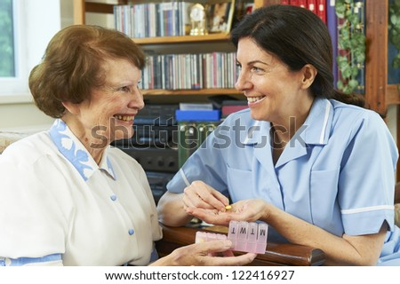 Nurse looking at elderly woman and giving her pills - stock photo