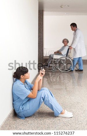 Nurse looking at her mobile phone while sitting in the hallway - stock photo