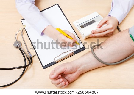 nurse measures blood pressure of patient during appointment - stock photo