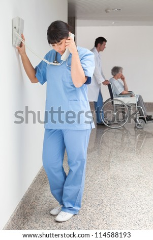 Nurse on telephone in hallway while doctor pushes patient in wheelchair - stock photo