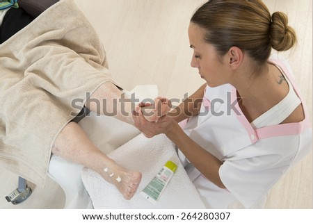 Nurse or care giver massaging foot   of an elderly woman - stock photo