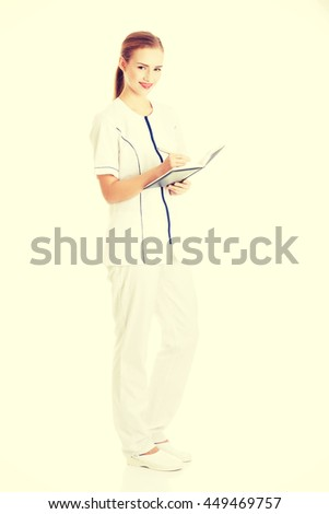 Nurse or doctor is writing in a notebook. - stock photo