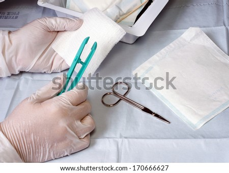 Nurse prepares wound dressing tray materials for use on a patient. - stock photo