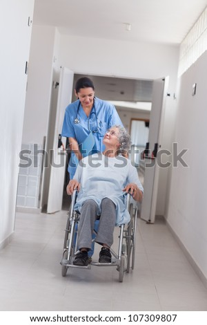 Nurse pushing a patient in a wheelchair in hospital ward - stock photo