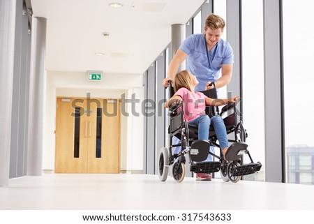 Nurse Pushing Girl In Wheelchair Along Corridor - stock photo