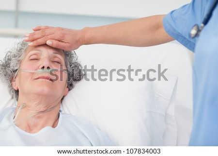 Nurse putting her hand on the forehead of a patient in hospital ward - stock photo