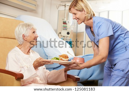 Nurse Serving Meal To Senior Female Patient Sitting In Chair - stock photo