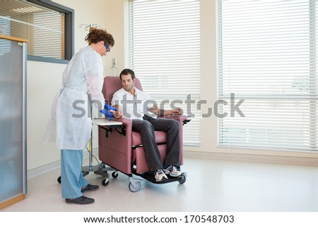 Nurse setting up chemotherapy treatment in oncology department - stock photo