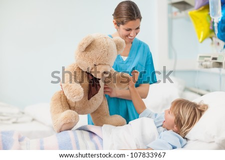 Nurse showing a teddy bear to a child in hospital ward - stock photo