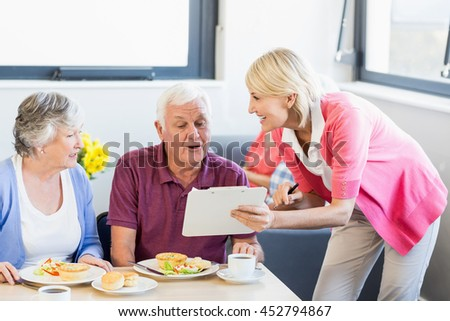 Nurse showing clipboard to seniors in a retirement home - stock photo
