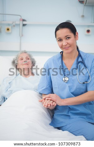 Nurse sitting on the bed next to a patient in hospital ward - stock photo